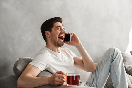 Positive brunette man in basic t-shirt laughing while talking on cell phone and holding cup with tea at home