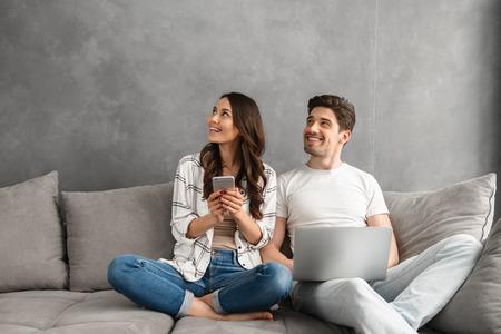 hermoso hombre y mujer sentada juntos en el sofá en el interior gris y mirando a otro lado en el copyspace mientras que usa la computadora portátil y el teléfono inteligente
