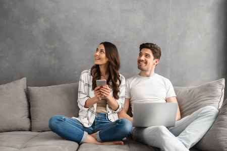 Beautiful man and woman sitting together on couch in gray interior and looking aside on copyspace while using laptop and smartphone