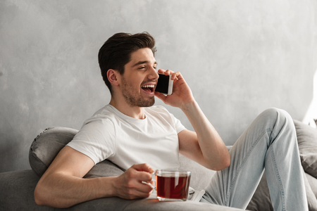 Young and beautiful man in basic t-shirt smiling and speaking on mobile phone while drinking tea on couch in house
