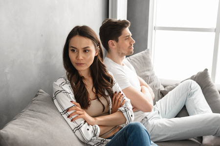 Photo of resentful guy and girl acting like arguing couple and not speaking to each other, while sitting together on couch at home isolated over white background