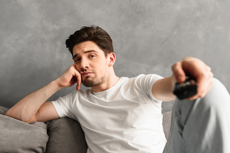 Photo closeup of upset man sitting on couch at home and showing remote control on camera