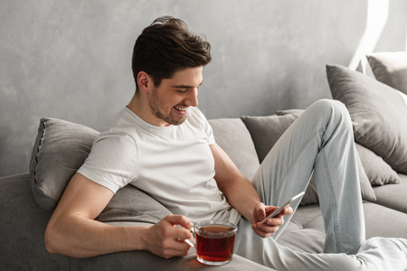 Handsome man in basic t-shirt smiling and holding mobile phone in hands while drinking tea on couch in house