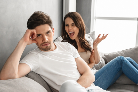 Photo of disappointed couple sitting together on sofa at home with upset look while woman screaming on man isolated over white background