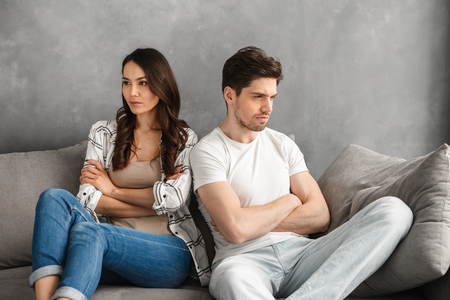 Photo of resentful guy and girl acting like arguing couple and not speaking to each other, while sitting together on sofa with crossed hands isolated over white background 스톡 콘텐츠