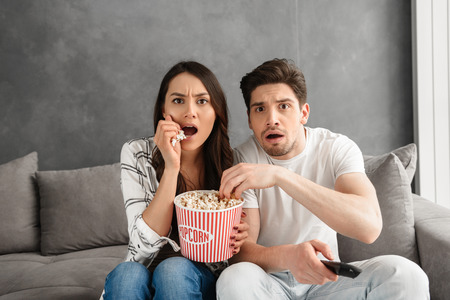 Image of anxious family sitting on sofa at home and looking at you while watching scary movie and eating popcorn Stock Photo