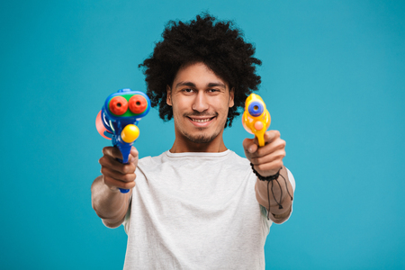 Portrait of a smiling young african man playing with two water guns isolated over blue background Stock Photo