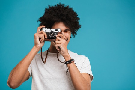 Picture of handsome emotional young african curly man photographer isolated over blue wall background holding camera. Stock Photo