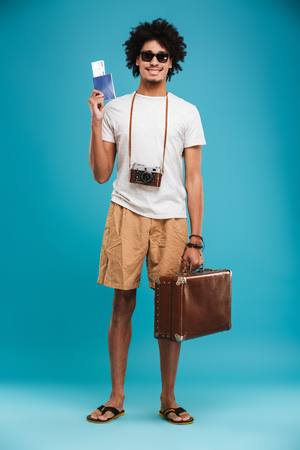 Picture of handsome happy young african curly man tourist isolated over blue wall background holding tickets with passport and suitcase. Stock Photo