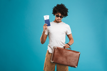 Photo of handsome young african curly man tourist isolated over blue wall background holding tickets with passport and suitcase. Stock fotó