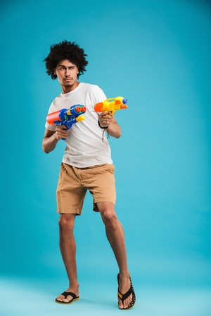 Full length portrait of a happy young african man playing with two water guns isolated over blue background