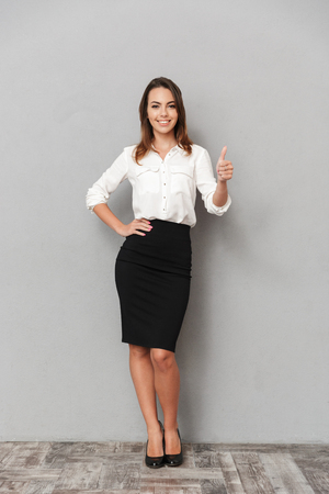 Full length portrait of a smiling young business woman showing thumbs up over gray background