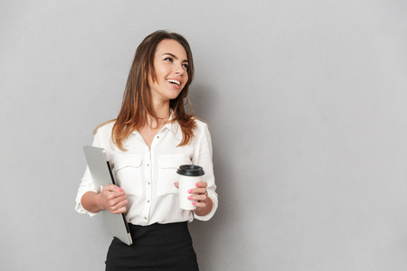 Portrait of a happy young business woman looking away while holding laptop computer and cup of coffee to go isolated over white background Stock Photo