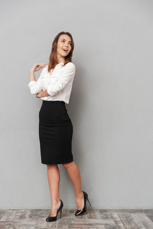 Image of beautiful business woman standing isolated over grey background looking aside. Фото со стока