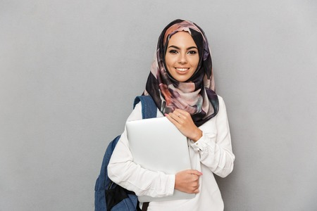 Portrait of a smiling young arabian woman student with backpack holding laptop computer isolated over gray background
