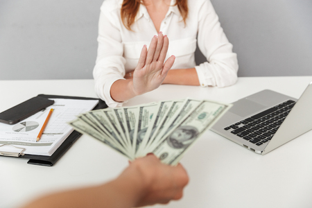 Close up portrait of hand holding cash bribe in front of a female office worker isolated. Businesswoman saying no 스톡 콘텐츠