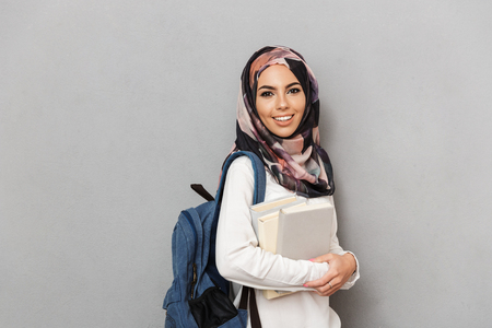Portrait of a happy young arabian woman student with backpack holding books isolated over gray background