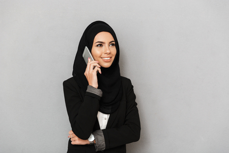 Portrait of a smiling young arabian woman talking on mobile phone isolated over gray background Фото со стока
