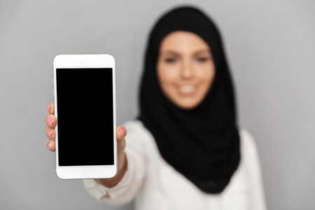 Blurry image of smiling muslim woman 20s in islamic headscarf with oriental makeup demonstrating closeup cell phone at camera isolated over gray background