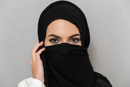 Close up portrait of a young arabian woman wearing hijab looking at camera isolated over gray background 写真素材
