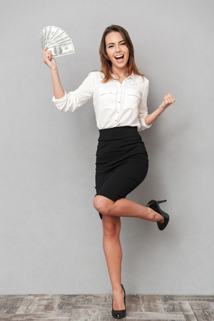 Photo of excited young business woman standing isolated over grey wall background make winner gesture holding money. Stock Photo