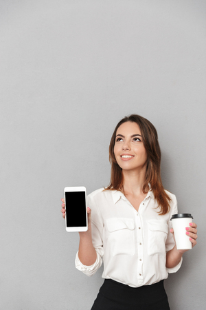 Portrait of a lovely young business woman showing blank screen mobile phone while holding cup of coffee to go and looking up isolated over white background Stock Photo