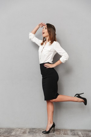 Image of beautiful business woman standing isolated over grey background looking aside. Stock Photo