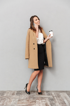 Image of cheerful young business woman standing isolated over grey wall background holding coffee talking by phone.