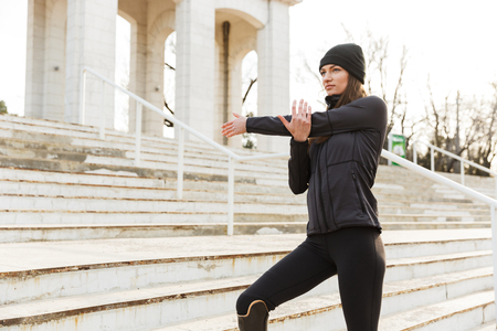 Closeup image of beautiful handicapped sportswoman in tracksuit with prosthesis warming up and stretching at the stairs outside Stock Photo
