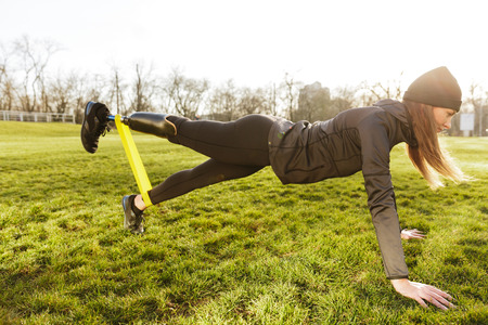 Image of sporty handicapped woman in black tracksuit warming up and doing plank with prosthesis leg on nature using rubber band Stock Photo