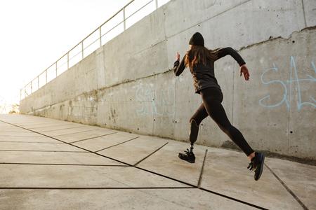 Portrait de femme athlète handicapé avec jambe prothétique en survêtement le long du mur de béton à l'extérieur