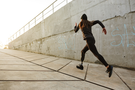 Portrait of disabled athlete woman with prosthetic leg in tracksuit running along concrete wall outside