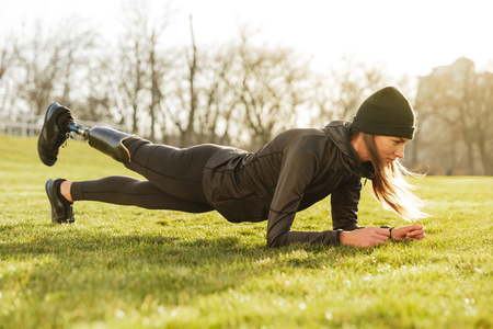 Image of sporty handicapped woman in black tracksuit warming up and doing plank with prosthesis leg on nature