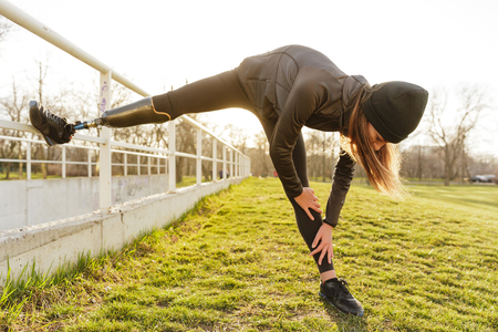 Photo of disabled running woman in sportswear doing slopes and stretching prosthetic leg on grass using railing