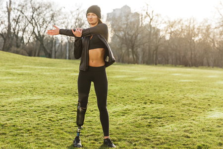 Image of beautiful handicapped sportswoman in tracksuit with prosthesis leg warming up and stretching arm on nature Stock Photo