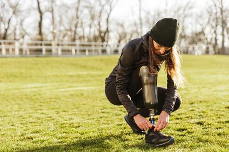 Afbeelding van jonge gehandicapte sportvrouw in trainingspak gehurkt en schoenveters binden op prothese been buiten