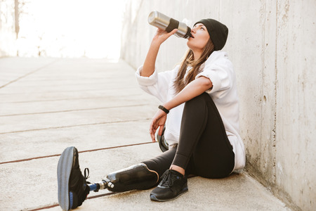 Photo of attractive young handicapped woman having bionic leg in streetwear, sitting on concrete floor outdoor and drinking water from metal cup