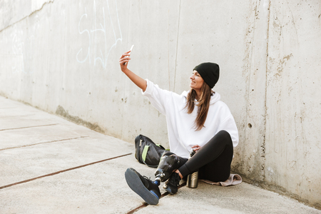 Photo of modern young handicapped woman in streetwear having bionic leg sitting on concrete floor outdoor and taking selfie on smartphone