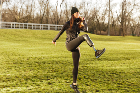 Image of happy handicapped woman 20s in tracksuit doing sports on nature and raising prosthesis leg Stockfoto