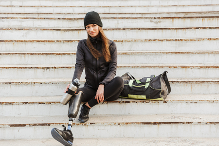 Photo of smiling handicapped woman in sportswear with prosthetic leg sitting at the stairs outdoor and holding  cup