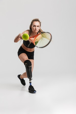 Image of a strong young disabled sportswoman tennis player standing isolated over grey background play tennis.