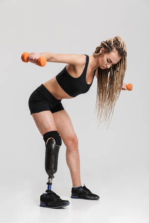 Image of a healthy young disabled sportswoman standing isolated over grey background make exercises with dumbbells. Stock Photo