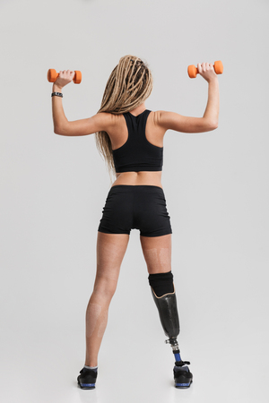 Back view photo of a healthy young disabled sportswoman standing isolated over grey background make exercises with dumbbells.