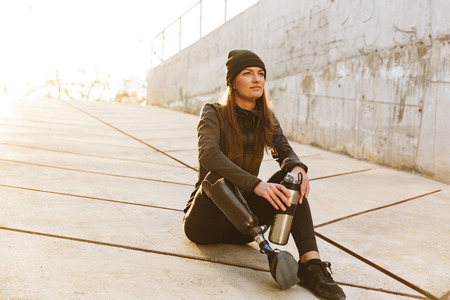 Photo of athletic disabled girl with prosthetic leg in sportswear sitting on concrete floor outdoors and looking aside Stockfoto