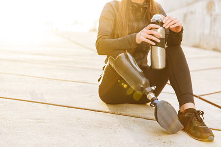 Cropped photo of athletic disabled girl with prosthetic leg in sportswear sitting on concrete floor outdoors and holding  cup