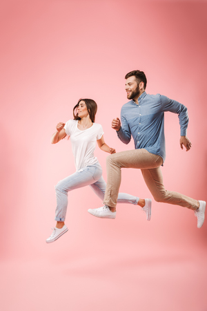 Full length portrait of a funny young couple running fast isolated over pink background Stock Photo - 102275542