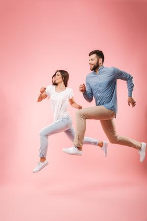 Volledig lengteportret van een grappig jong paar die snel lopen geïsoleerd over roze achtergrond