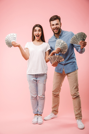 Full length portrait of a cheerful young couple holding bunch of money banknotes and celebrating success isolated over pink background