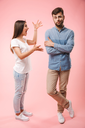Full length portrait of a mad young couple having an argument isolated over pink background