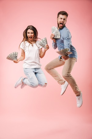 Full length portrait of an excited young couple holding bunch of money banknotes and celebrating success while jumping isolated over pink background